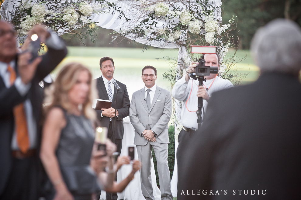 grooms face as bride walks down aisle