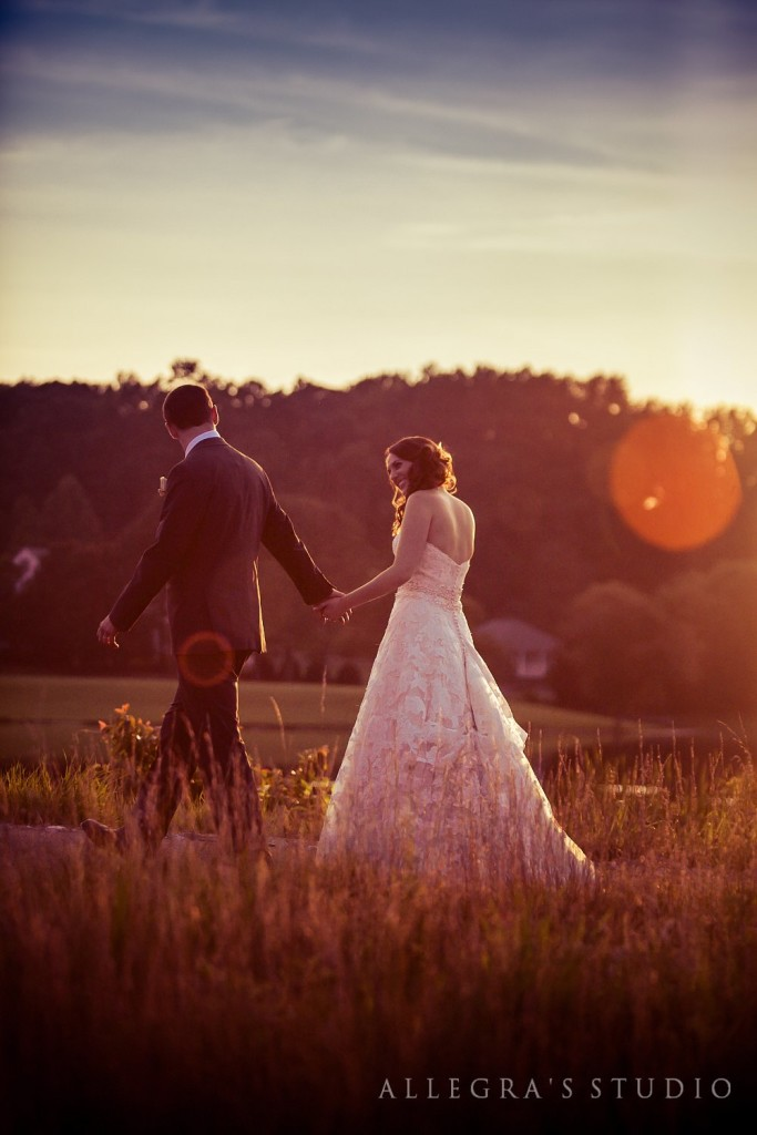 Couple walks in field at sunset